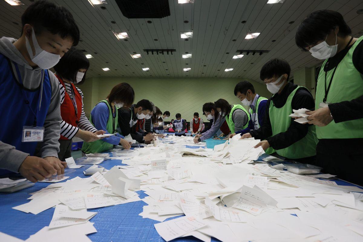 写真・図版 : 熊本県知事選で、マスクを着用し、投票用紙を仕分ける市職員ら=2020年3月22日午後9時18分、熊本市中央区