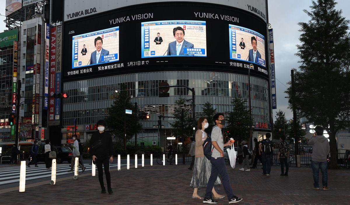 写真・図版 : 緊急事態宣言の延長が決まり、街頭の大型ビジョンに安倍晋三首相の記者会見が映し出された=2020年5月4日午後6時1分、東京都新宿区