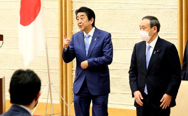 写真・図版 : 会見を終え、記者からの呼びかけに答える安倍晋三首相(中央)。右は菅義偉官房長官=2020年5月4日、首相官邸