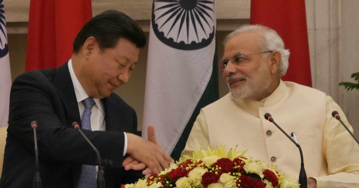 写真・図版 : 握手するインドのモディ首相(右)と中国の習近平主席=2014年9月18日、ニューデリー