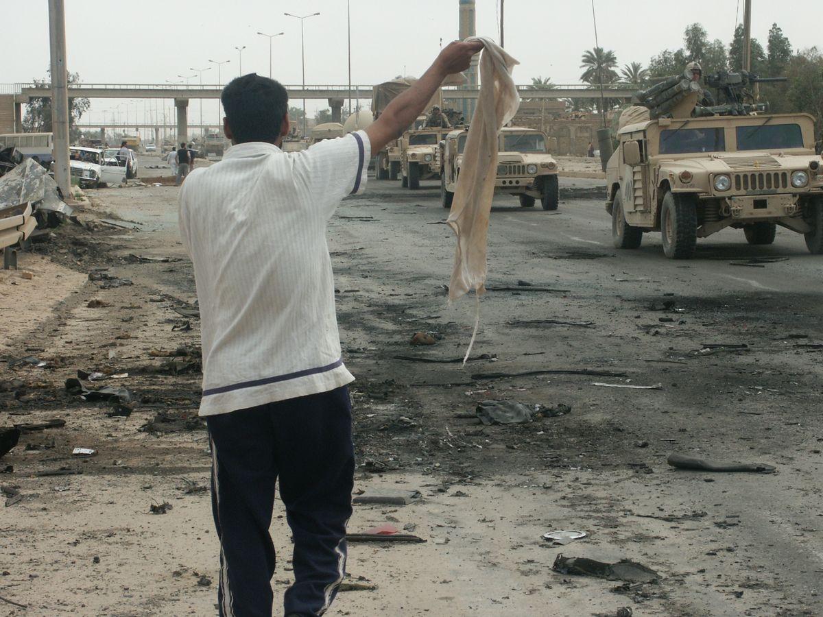 写真・図版 : イラク戦争で陥落した直後のバグダッドで、米軍に白い布を振り無抵抗の意志を示すイラク人=2003年(筆者撮影)