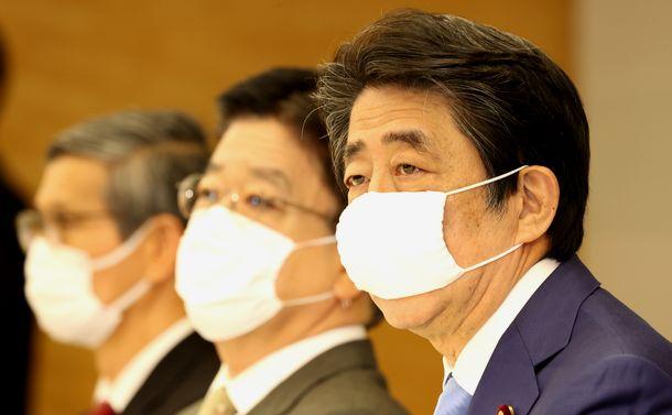 写真・図版 : 新型コロナウイルス感染症対策本部の会合で、緊急事態宣言の延長について説明する安倍晋三首相(右)。左は専門家会議の尾身茂副座長、中央は加藤勝信厚労相=2020年5月4日
