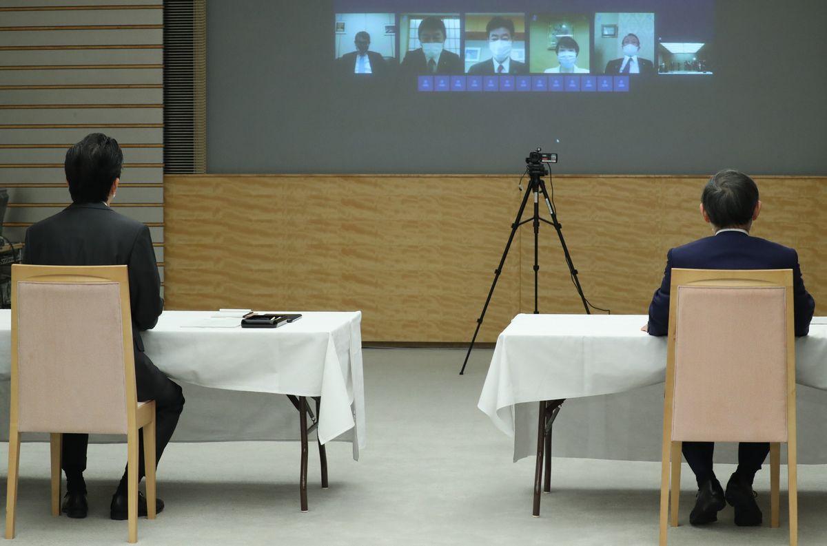 写真・図版 : テレビ会議形式で行われる閣議に臨む安倍晋三首相(左)。右は菅義偉官房長官=2020年5月1日、首相官邸