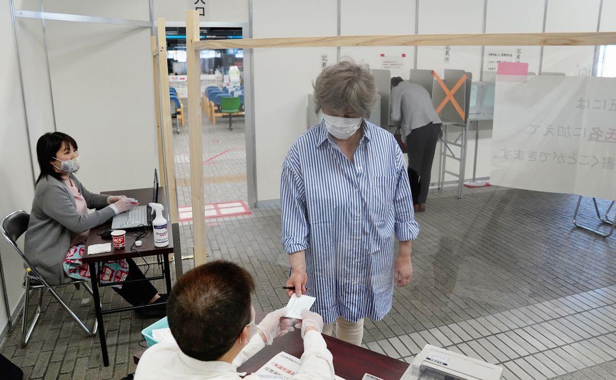 写真・図版 : 新型コロナウイルス感染予防のため、木枠に張られた透明なビニールの下から投票用紙を受け取る有権者=2020年4月26日、静岡市清水区