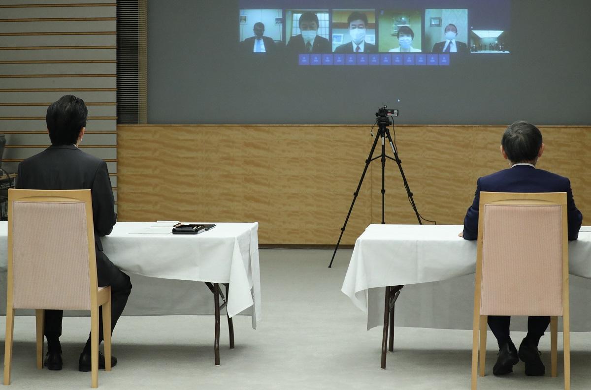 写真・図版 : テレビ会議形式で行われた閣議に臨む安倍晋三首相(左)と菅義偉官房長官=2020年5月1日