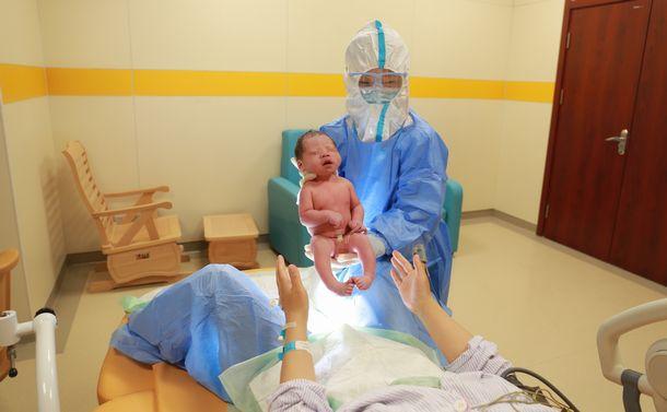 写真・図版 : 中国河北省の石家荘市第四病院の助産師のWang Xueliは、COVID-19感染拡大期間中のハイリスク出産の責任者。分娩後の母親に生まれたばかりの赤ちゃんを見せている様子。「この特別な状況では、すべての医療従事者が厳格で高度な感染予防策を講じています。 感染が疑われ隔離された女性の出産に立ち会う場合、私たちも心配はしますが恐れはしません。専門的なスキルと自分たちの仕事への誇りを持って対処しています」 (写真:UNFPA中国事務所 / 中国母子保健協会)