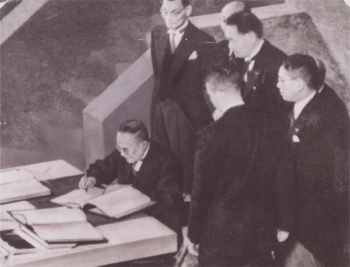写真・図版 : 首席全権として講和条約調印式で署名する吉田茂首相(左)=1951年9月、米国・サンフランシスコ