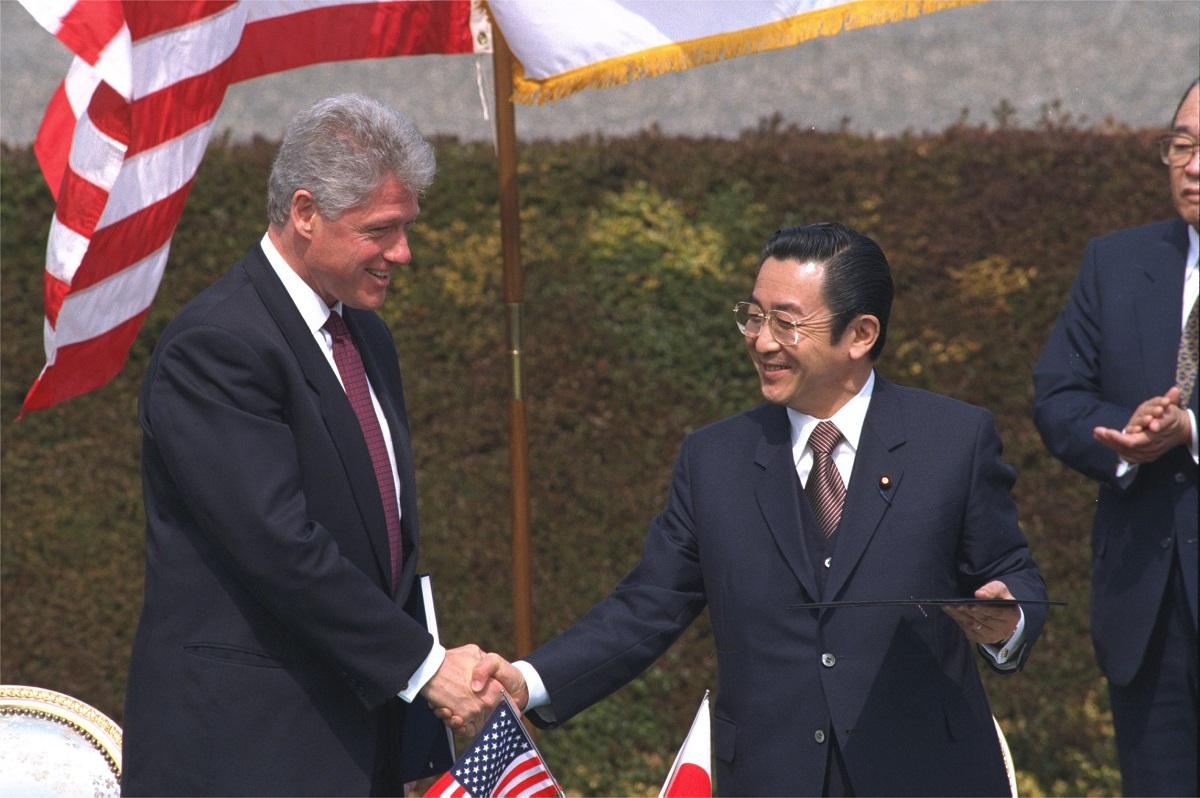 写真・図版 : 日米首脳会談で共同宣言に署名した後、クリントン大統領(左)と握手する橋本龍太郎首相=1996年4月、東京・迎賓館