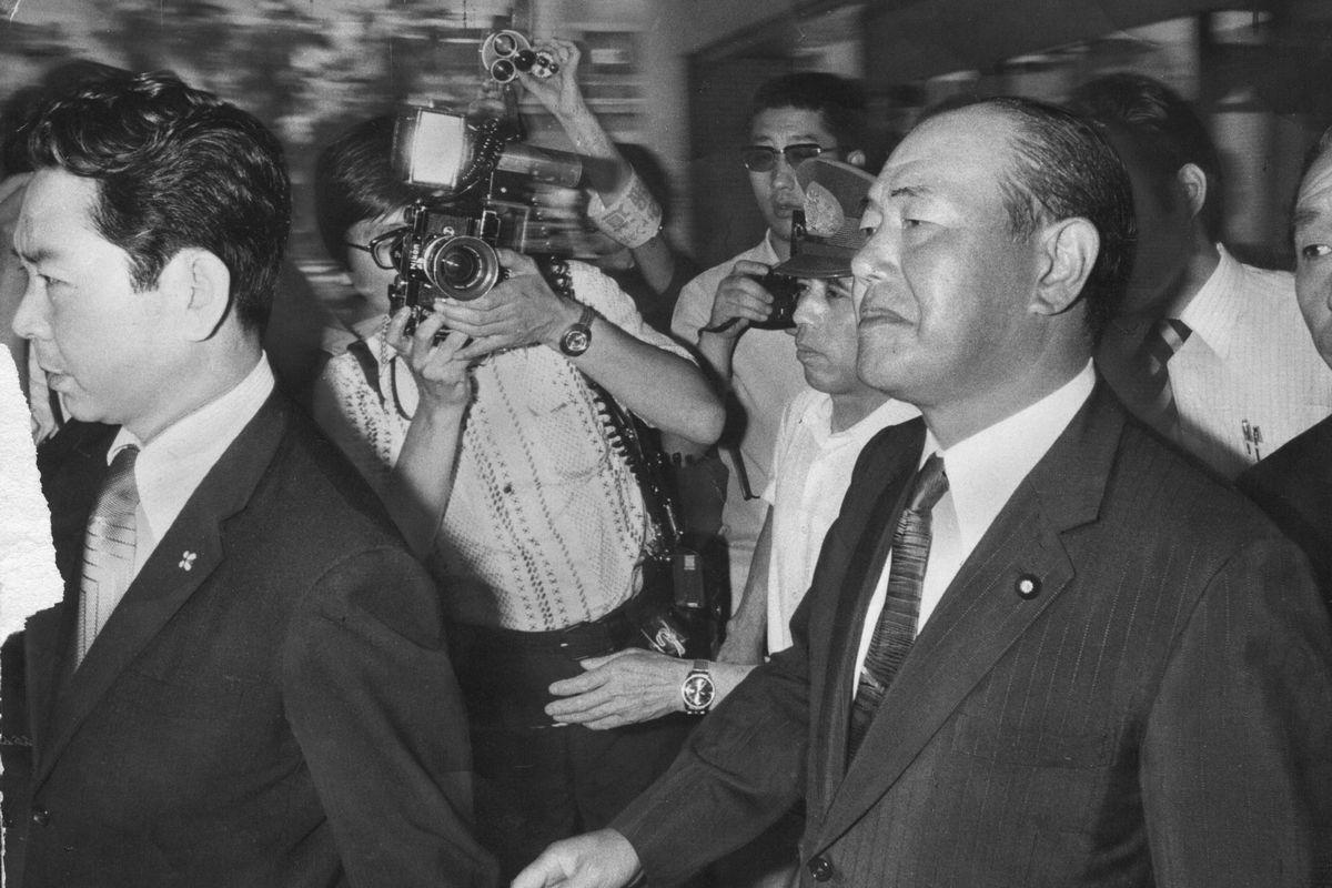 写真・図版 : ロッキード事件で、東京地検は田中角栄元首相に対し、外国為替及び外国貿易管理法違反の疑いで検察合同庁舎への任意同行を求め、取り調べ後に逮捕状を執行した。写真は、東京地検から東京拘置所へ向かう田中元首相=1976年7月27日