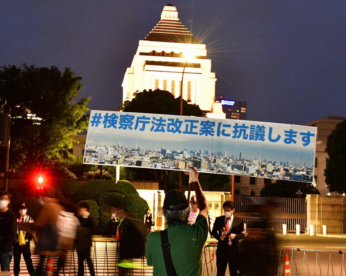 写真・図版 : 国会前でプラカードを上げて検察庁法改正案に抗議する人たち=2020年5月15日
