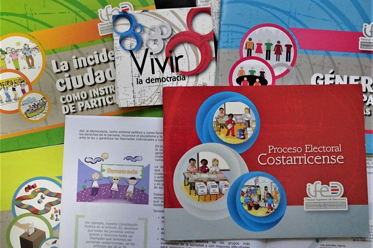 写真・図版 : コスタリカで民主主義教育を進める選挙最高裁判所が作成した小学生向けの教材。イラスト満載の冊子が7冊とボックスに入ったカードもある