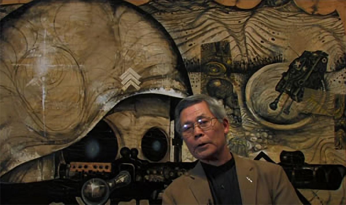 写真・図版 : 絵画「基地」の前で語る画家の中村宏さん(映画「ANPO」から)