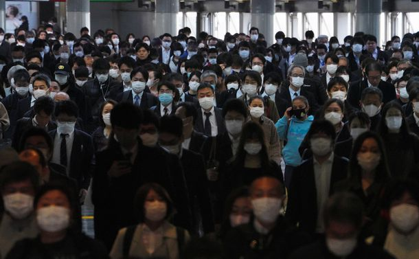写真・図版 : マスク姿の通勤客らの波が途切れることなく続くJR品川駅の自由通路=4月8日、鬼室黎撮影