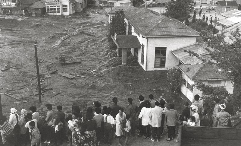 写真・図版 : 1960年チリ地震による津波を見つめる女川町の住民たち=撮影者不明
