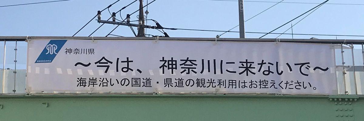 写真・図版 : 海岸沿いの国道や県道の観光利用を控えるよう「今は、神奈川に来ないで」と呼びかける神奈川県の横断幕が、湘南地方へ向かう国道にかかる