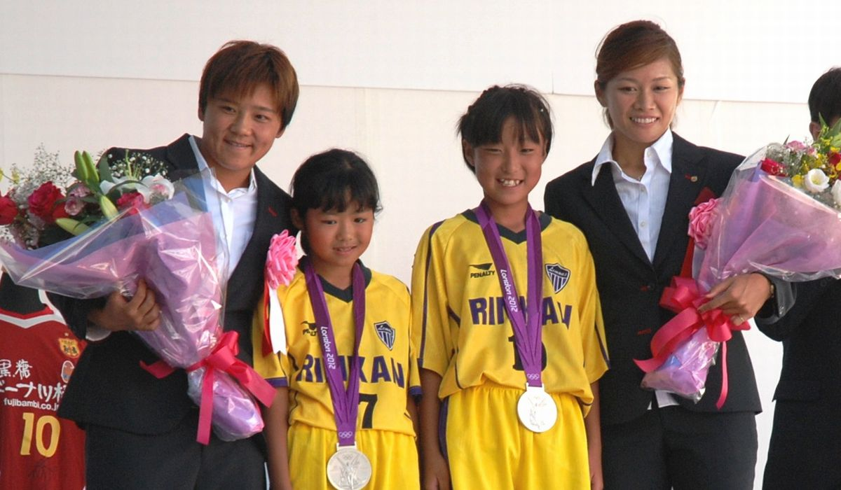 写真・図版 : 女子サッカーが盛んでワールドカップ優勝メンバーらを多く輩出。写真は、郷里の大和市で子供たちにメダルをかける大野忍、川澄奈穂美両選手