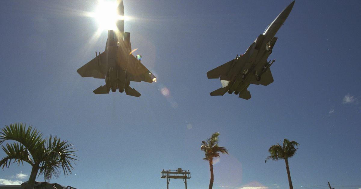 写真・図版 : 国道58号を横切り、米空軍嘉手納基地へ着陸するF15戦闘機=1995年、沖縄県嘉手納町。朝日新聞社