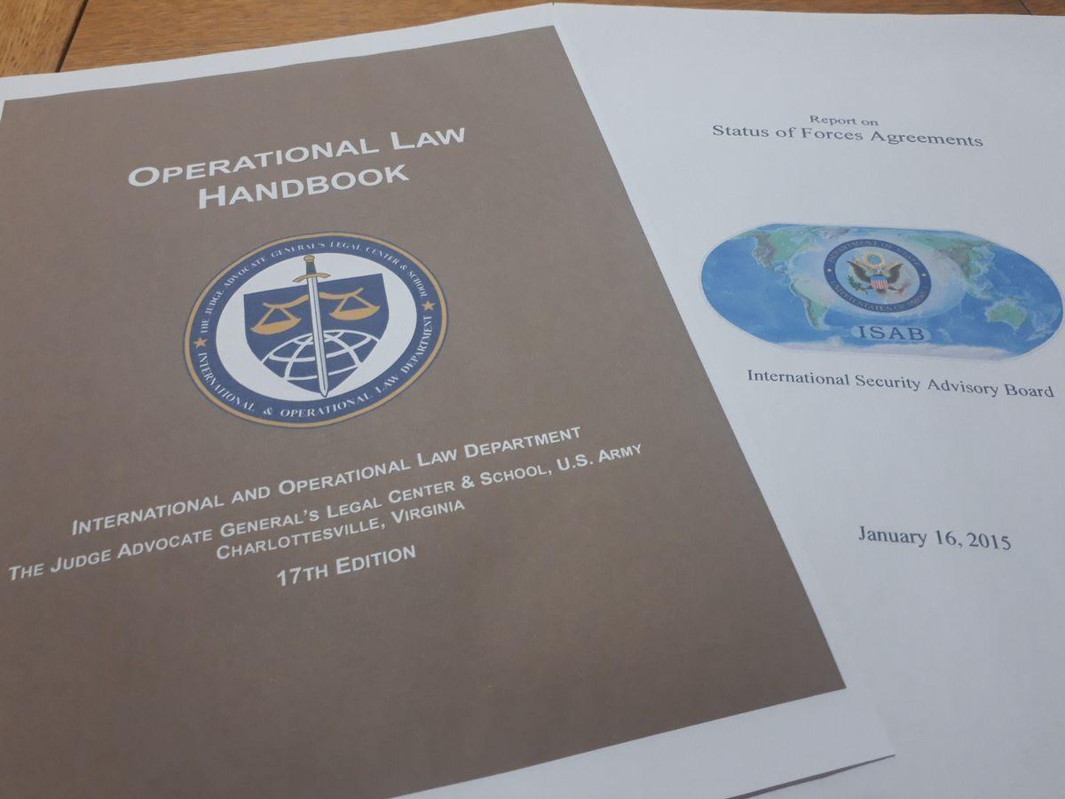 写真・図版 : 米政府諮問委員会が各国との地位協定を検証した2015年の報告書(右)と、米陸軍が軍法会議の判事を育てる機関が編んだ17年の「法運用ハンドブック」の表紙