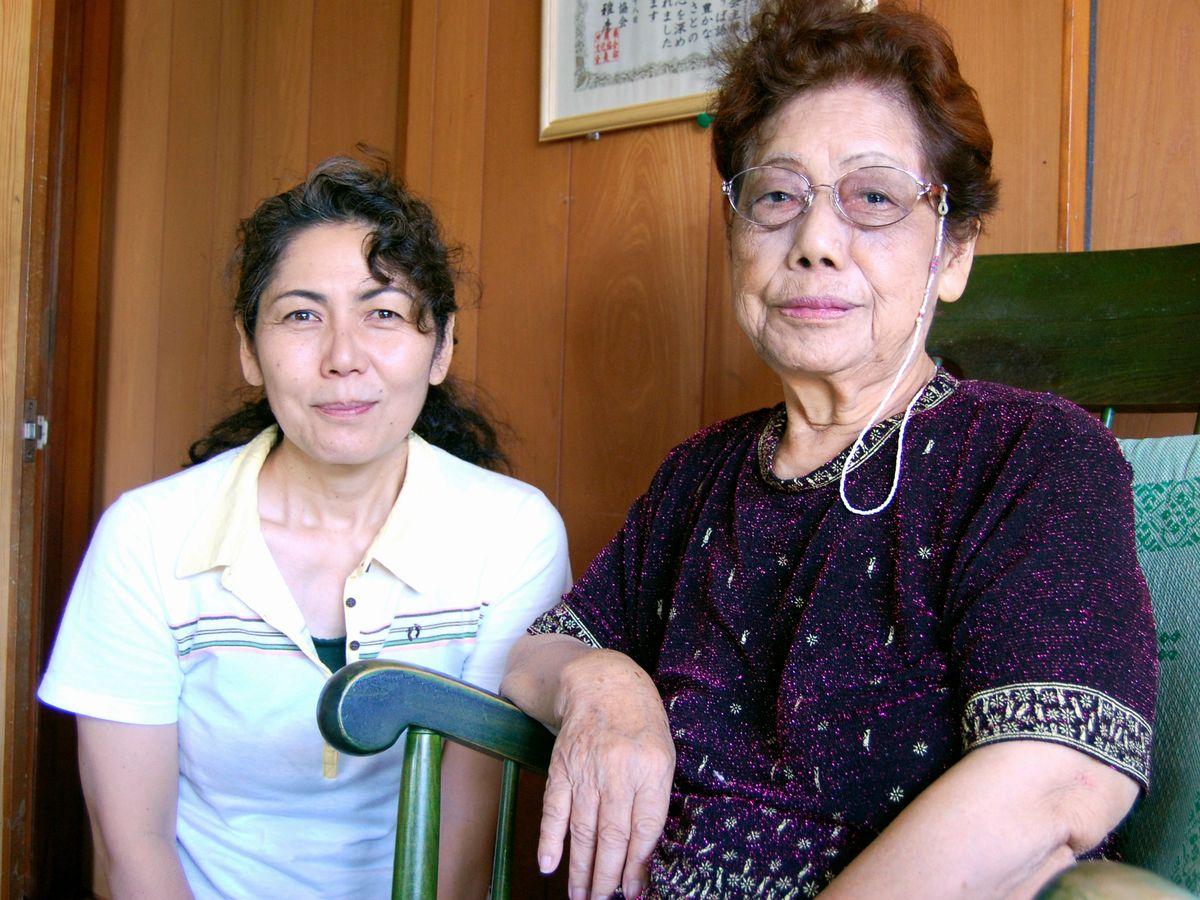 写真・図版 : 沖縄戦の語り部をしていた宮城巳知子さん(右)。2015年に亡くなった。左は次女の孝子さん=11年6月、沖縄県嘉手納町屋良の巳知子さん宅。藤田撮影