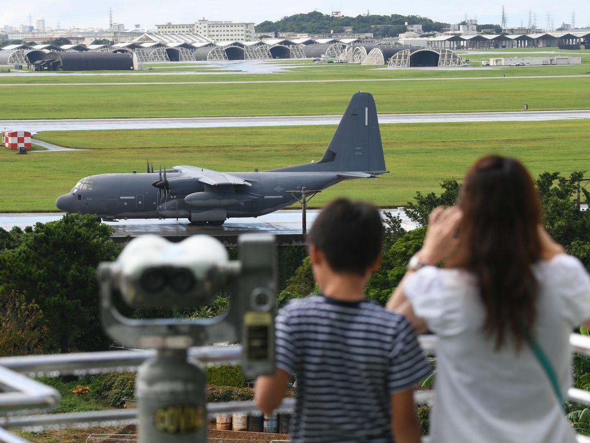 写真・図版 : 米空軍嘉手納基地を「道の駅かでな」の展望台から見る人たち=2018年、沖縄県嘉手納町。朝日新聞社