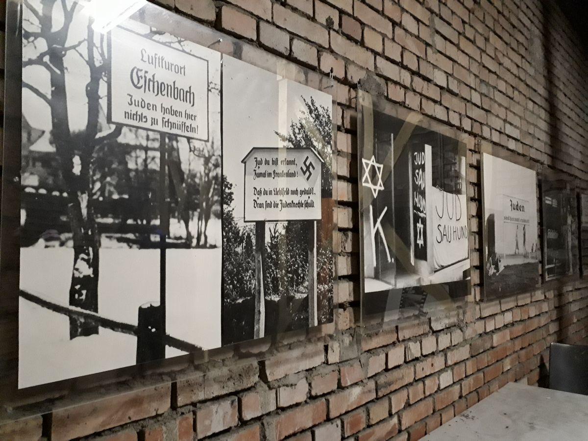 写真・図版 : 「黄金の間」の脇の壁に並ぶ、かつてユダヤ人を差別した街角の看板などの写真パネル