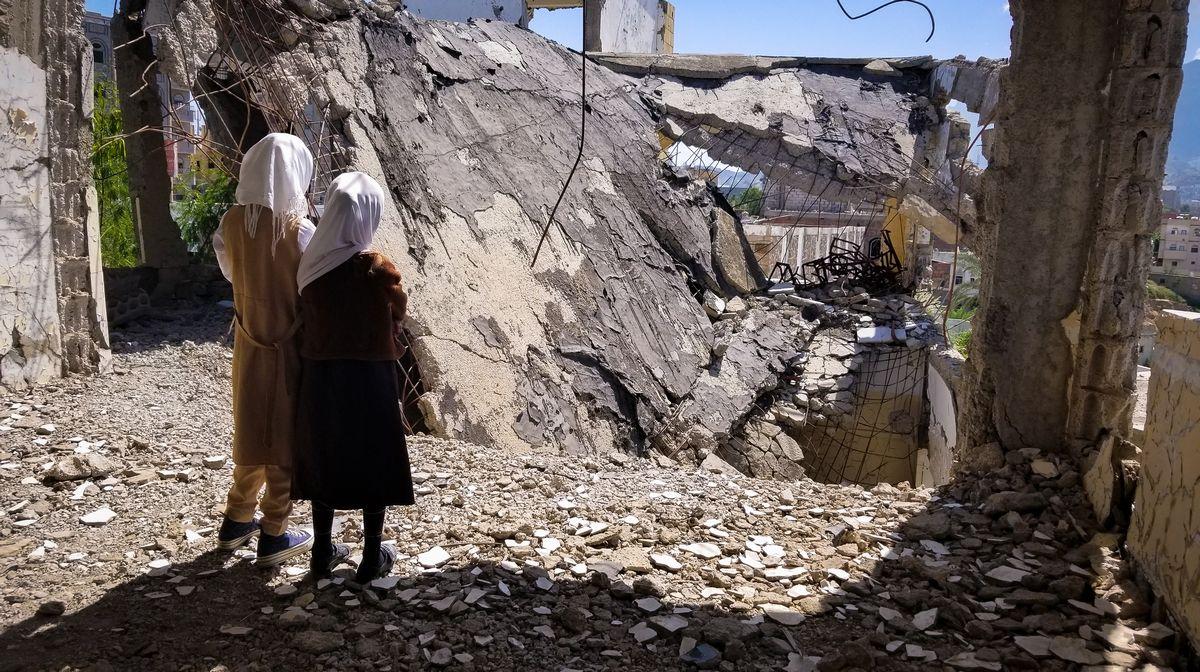 写真・図版 : 内戦で破壊されたイエメンの学校。がれきの上に立つ子どもたち(anasalhajj/shutterstock)