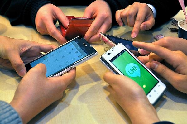 写真・図版 : スマホを手にネットを使う高校生たち=高見澤恵理撮影