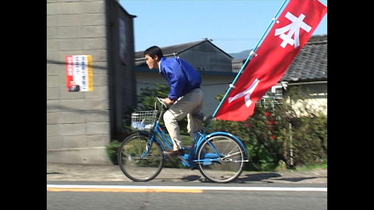 写真・図版 : 2003年 自転車に乗って選挙活動