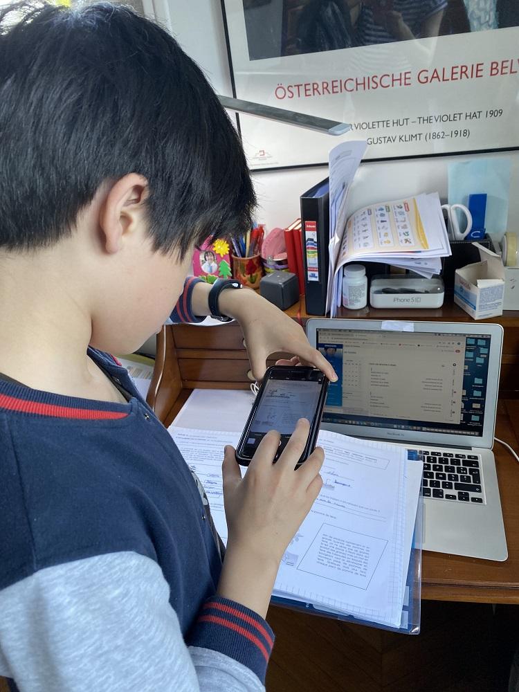 写真・図版 : やり終えた課題をスマートフォンで写真に撮り、担任の教師にメール添付で送るフランスの中学1年生の男の子(日本の小学6年生に相当)=パリ郊外で