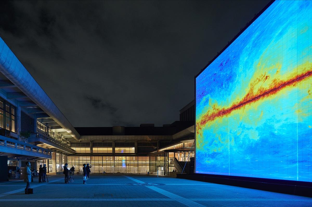 写真・図版 : 池田亮司の 『the radar[kyoto]』。ロームシアター京都の中庭に巨大なスクリーンを設置し、その地点から観測できる宇宙のデータを音声と映像で表現した=2016年、浅野豪撮影