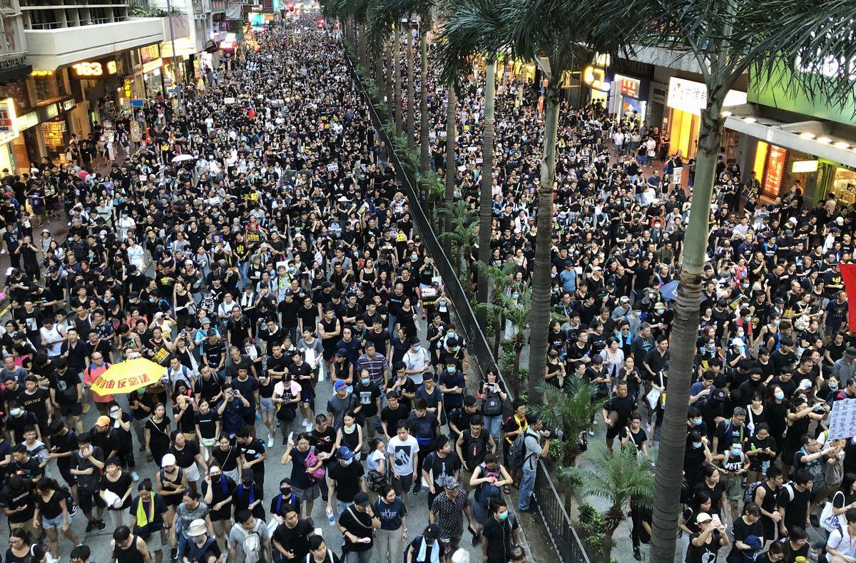写真・図版 : 「逃亡犯条例」改正案の撤回を求めるデモ行進の参加者ら=2019年7月21日、香港、益満雄一郎撮影