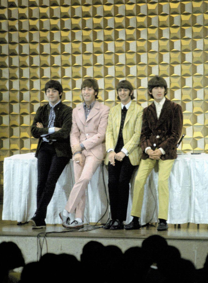 写真・図版 : 1966年の来日時、旧東京ヒルトンホテルの「真珠の間」で記者会見を前に写真撮影のポーズをとるビートルズの4人。旧東京ヒルトンは、国内外のVIPの利用でも名高かった