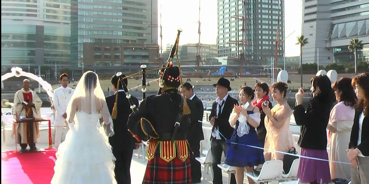 写真・図版 : パーティー船上でのバグパイプ結婚式で演奏する筆者