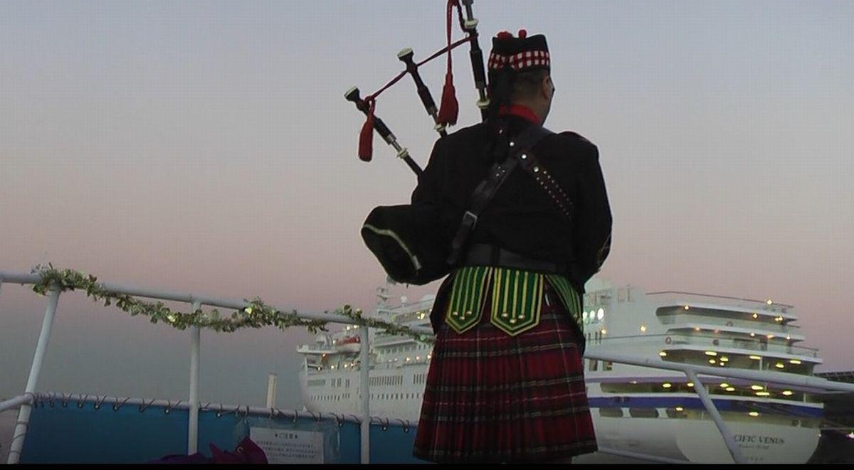 写真・図版 : 横浜港沖をクルーズする船の上でバグパイプを吹く筆者