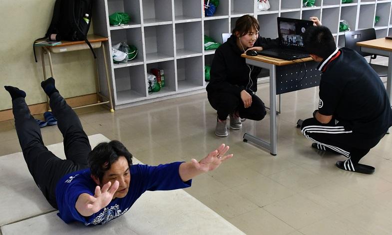写真・図版 : 体育の授業の動画配信。補助教員がカウントを取ったり、カメラの角度を調整したりする=2020年5月12日、佐賀市水ケ江の龍谷中学・高校、松岡大将撮影