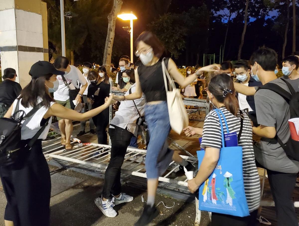 写真・図版 : 天安門事件の犠牲者を追悼するため、鉄柵を乗り越えて公園に入る市民たち=2020年6月4日