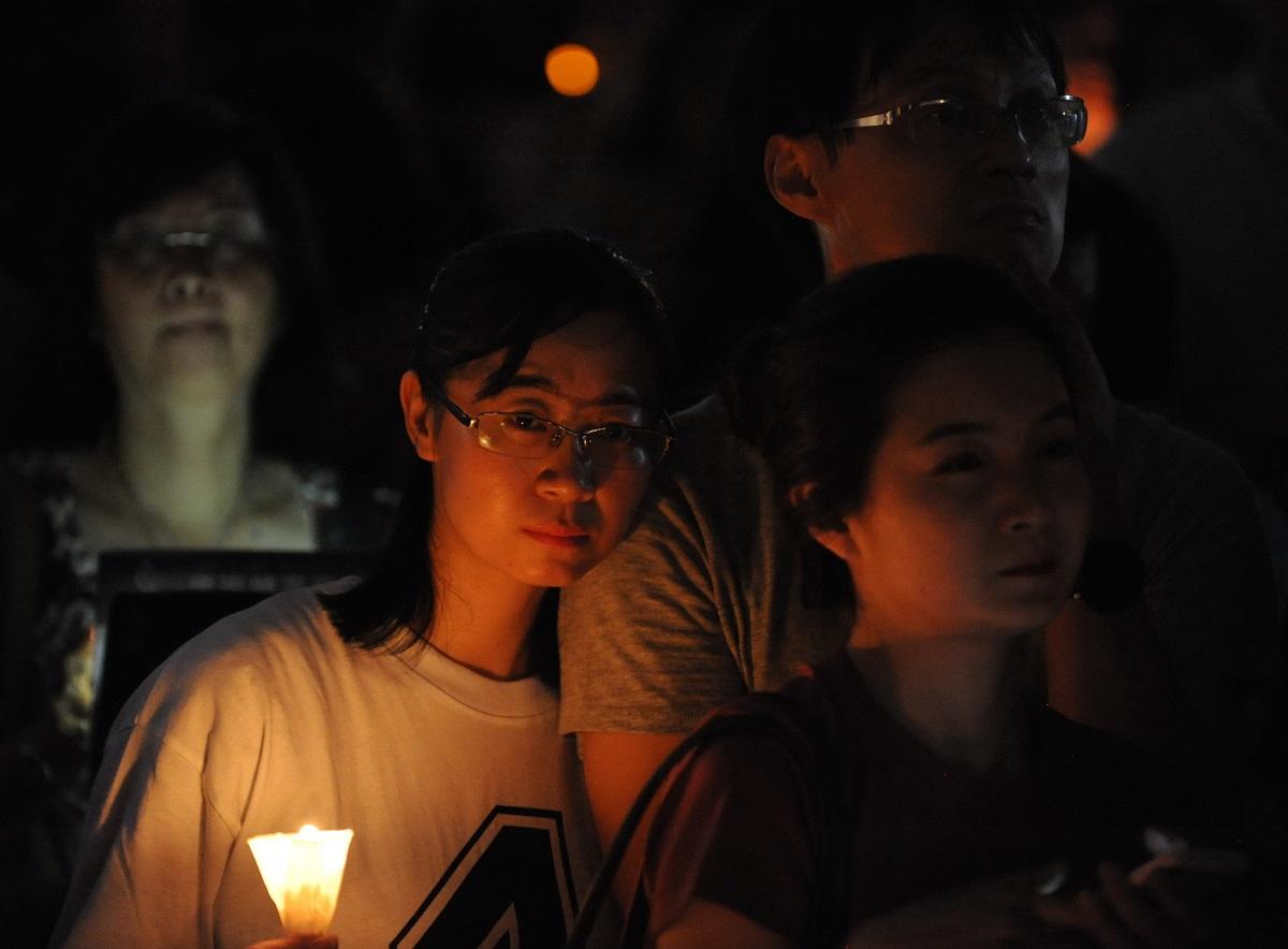写真・図版 : 天安門事件30周年の追悼集会でろうそくを手にする参加者。「6月4日を忘れない」といったプラカードが目立った=2019年6月4日、香港・ビクトリア公園