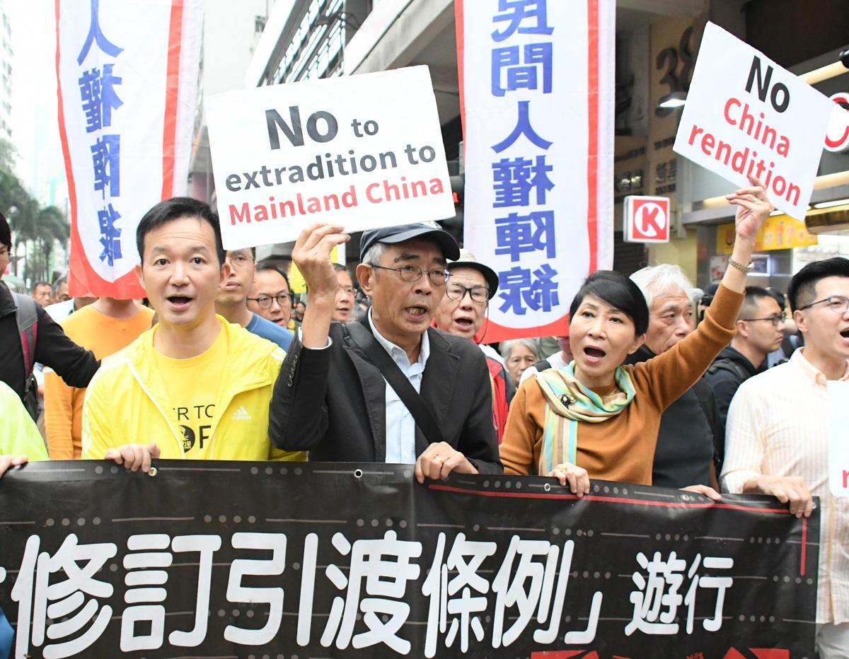 写真・図版 : 「逃亡犯条例」改正案に反対する民主派のデモ。前列左から2人目が銅鑼湾書店の元店長、林栄基氏=2019年3月31日、香港