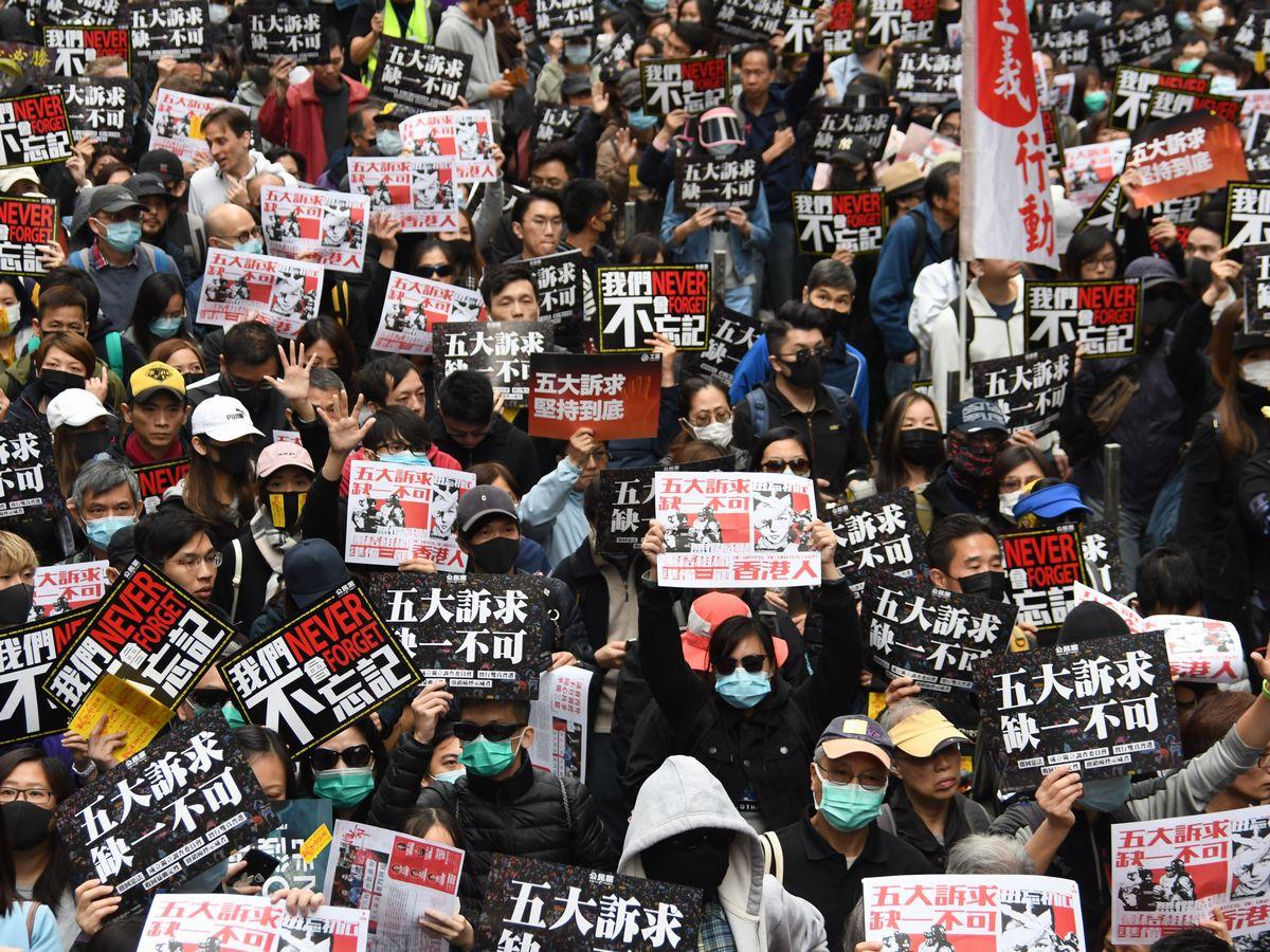 写真・図版 : 香港政府に抗議するデモ行進で大通りを埋め尽くす市民ら。この日のデモには100万人以上が参加した=2020年1月1日、香港・銅鑼湾
