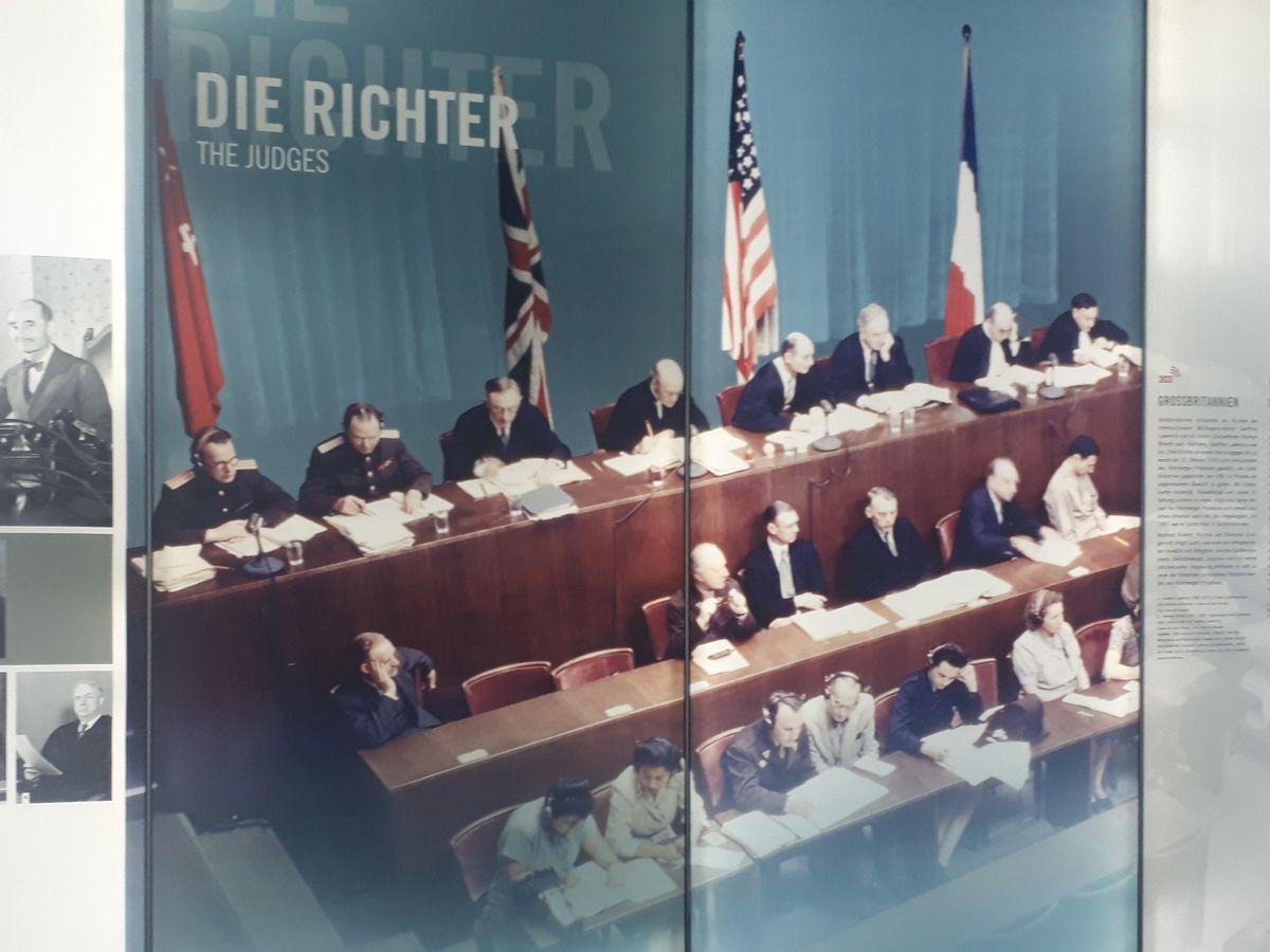 写真・図版 : ドイツのニュルンベルク国際軍事法廷記念館で、連合国の裁判官たちを紹介する展示