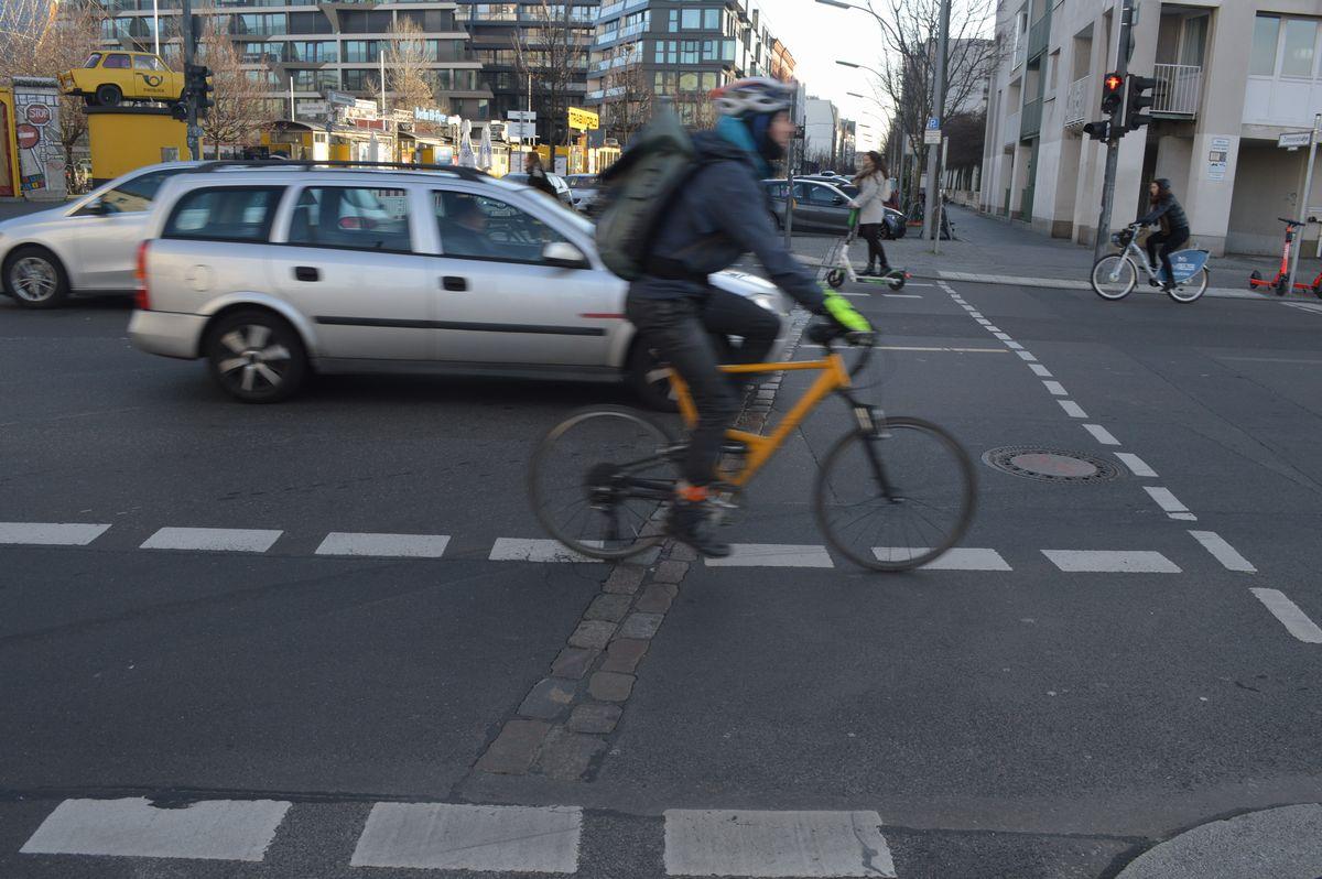 写真・図版 : ベルリン市街の交差点。自転車の後輪が掛かっているのが、ベルリンの壁の跡を示す線