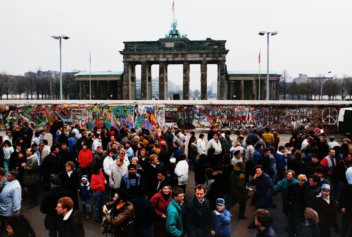 写真・図版 : 1989年11月の「ベルリンの壁」崩壊後初めての日曜、西側から壁とブランデンブルク門を見ようと集まった東側の市民たち=朝日新聞社