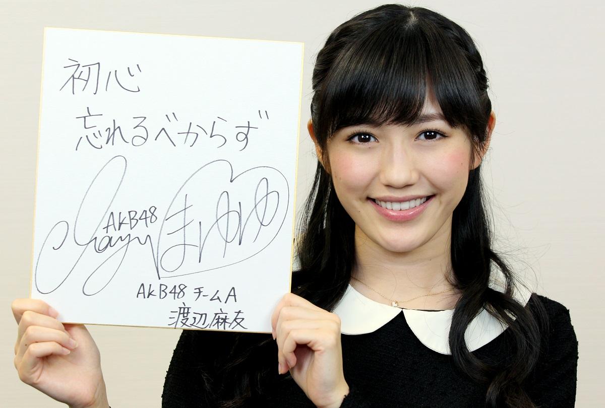 写真・図版 : 座右の銘を書いた色紙を手にする渡辺麻友さん=2014年