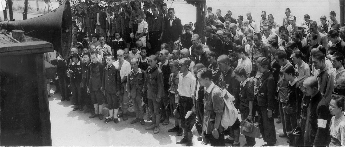 写真・図版 : 1945年8月15日、終戦を告げる玉音放送に聴き入る人たち=大阪・梅田の曽根崎警察署前。朝日新聞社