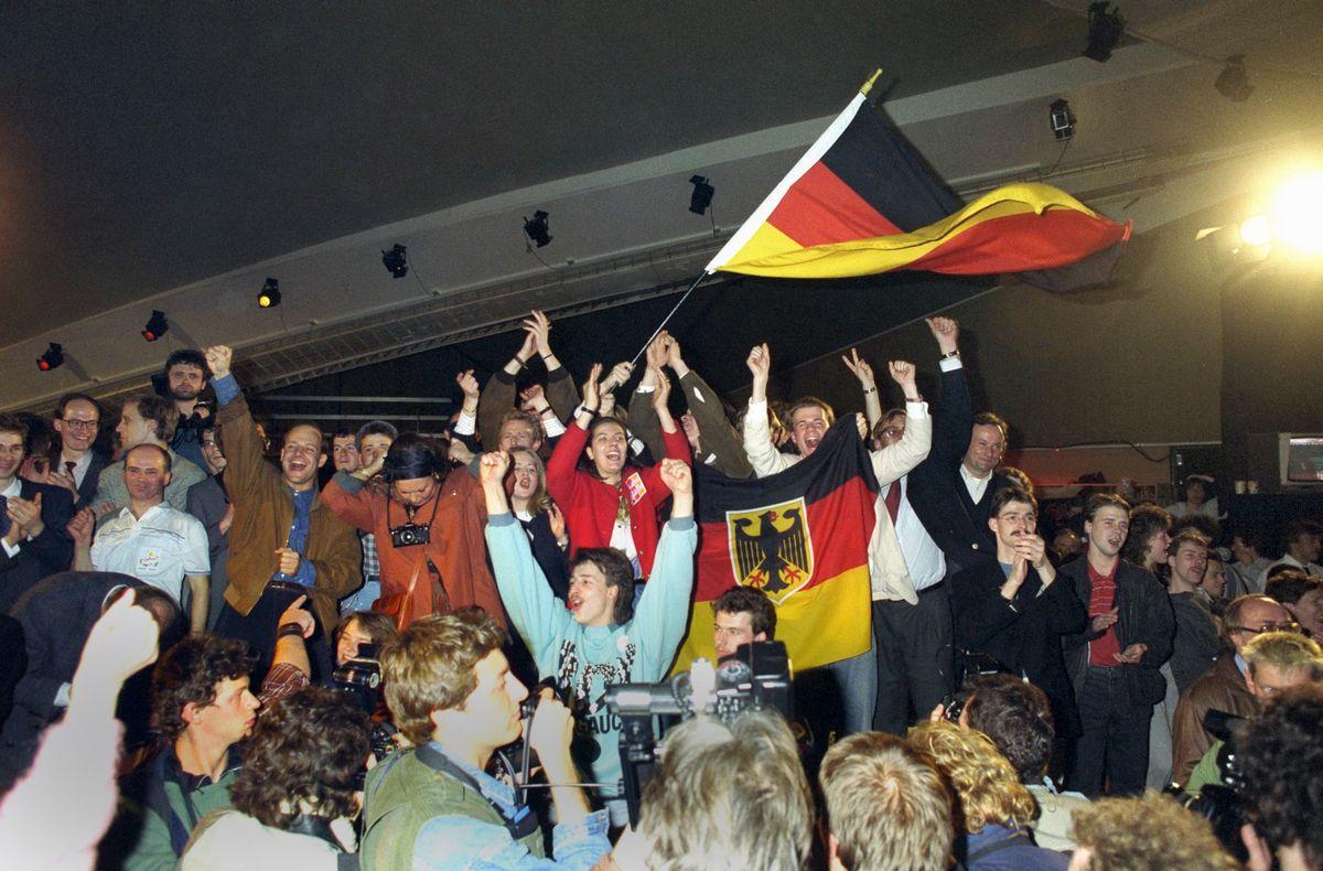 写真・図版 : 1990年3月、東ドイツの総選挙で西ドイツとの早期統一を求める勢力が勝ち、東ベルリンで西ドイツの国旗を振って喜ぶ人々=朝日新聞社