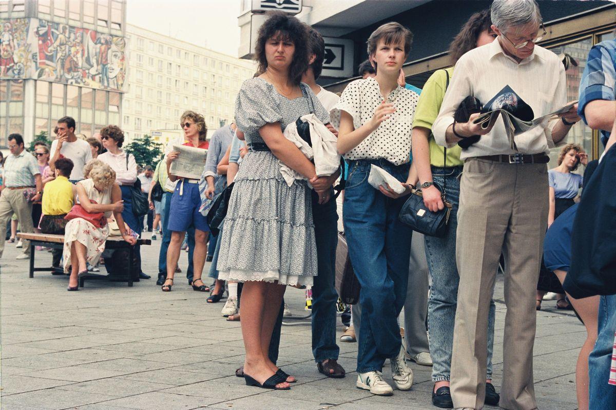 写真・図版 : 1990年7月、東ベルリンで再統一を控え、通貨を西ドイツ・マルクと交換しようと並ぶ人たち=朝日新聞社
