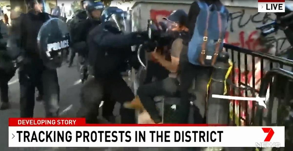 写真・図版 : 米ワシントンで6月1日、抗議デモを取材中のオーストラリアのテレビ局「チャンネル7」のカメラマン(中央右)を殴る警察官=同チャンネルのニュース映像から