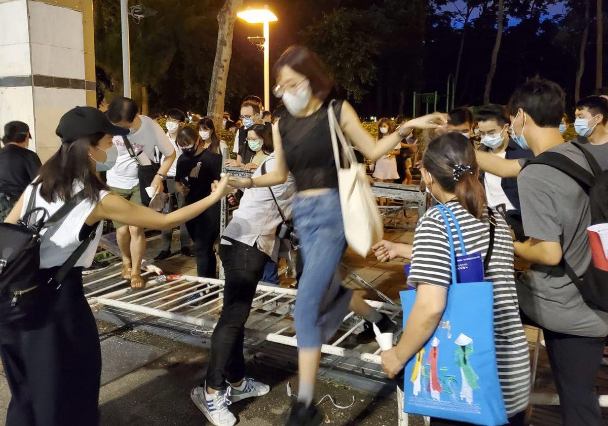 写真・図版 : 天安門事件の犠牲者を追悼するため、鉄柵を乗り越えて公園に入る香港の市民たち=2020年6月4日、香港、朱延雄撮影