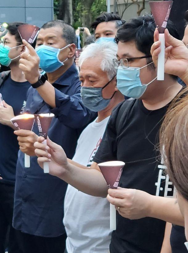 写真・図版 : ろうそくを掲げ、天安門事件の犠牲者を追悼する香港の民主派団体のメンバー=2020年6月4日、香港、朱延雄撮影