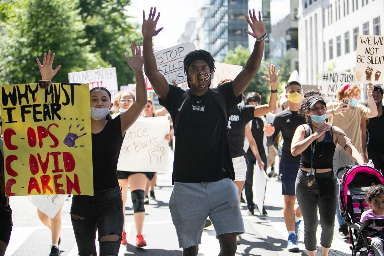 写真・図版 : 両手を挙げ「撃たないで」と叫びながら、ホワイトハウス周辺を行進するデモの参加者たち=ワシントン、ランハム裕子撮影、2020年5月31日